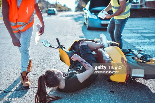 ambulance paramedics rushing to pull female from under motorcycle - motorcycle accident stock pictures, royalty-free photos & images