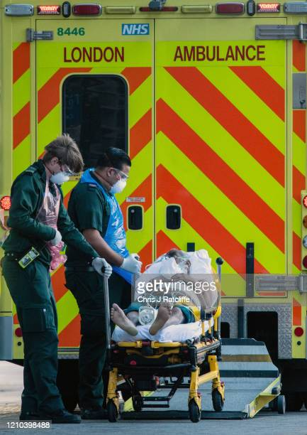 Ambulance paramedics wearing personal protective equipment help a patient from an ambulance into The Royal London Hospital on April 19, 2020 in...