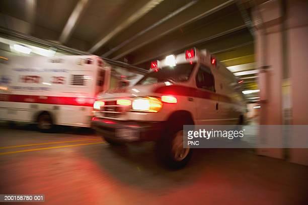 ambulance pulling away from hospital (blurred motion) - rettung stock-fotos und bilder