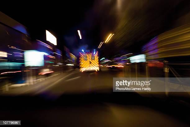 Ambulance rushing down street at night