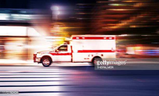ambulance speeding at night in new york city - emergencies and disasters stock pictures, royalty-free photos & images