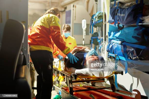 ambulance staff moving caucasian senior man on stretcher - ambulance stock pictures, royalty-free photos & images