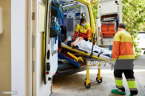 Ambulance Staff Moving Senior Man on Stretcher to Hospital