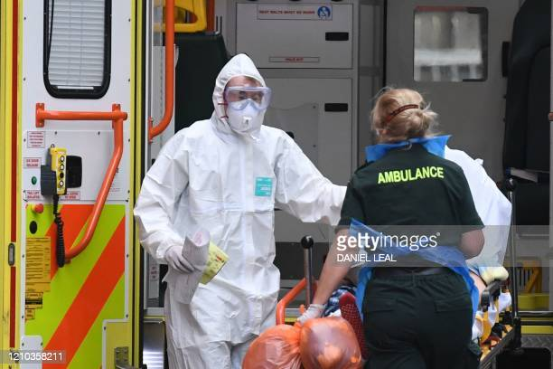 Ambulance staff wearing personal protective equipment help a patient from an ambulance into The Royal London Hospital in east London on April 18,...