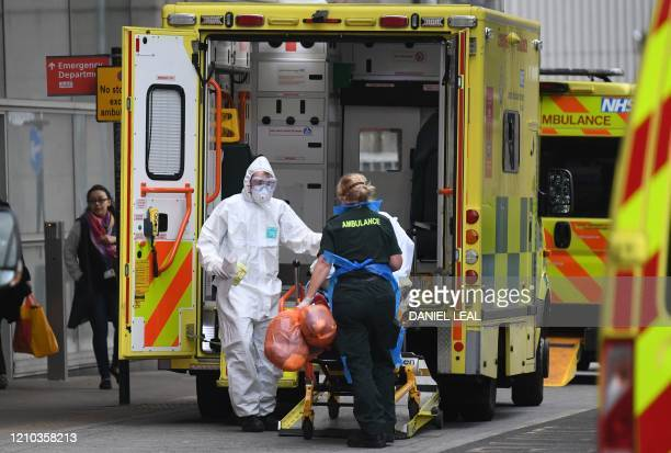 Ambulance staff wearing personal protective equipment help a patient from an ambulance into The Royal London Hospital in east London on April 18 2020...