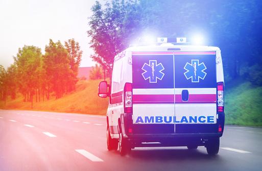 Ambulance van on highway with flashing lights 911803146
