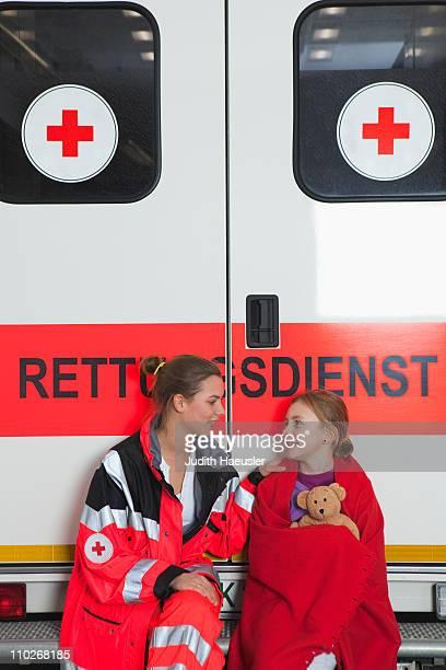 Ambulance woman calming girl at coach