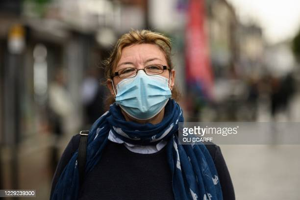Ambulance worker Louise Harvey is interviewed on the high street in Leigh, Greater Manchester, northwest England on October 22 as new restrictions...