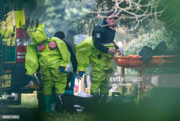 Ambulance workers are seen half dressed in protective suits in London Road cemetery as investigations continue into the poisoning of Sergei Skripal...