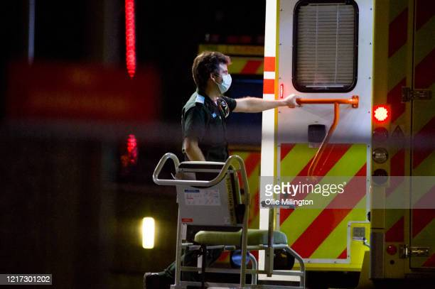 Ambulance workers transport patients outside St Thomas Hospital in Westminster, where British Prime Minister Boris Johnson has now been transferred...