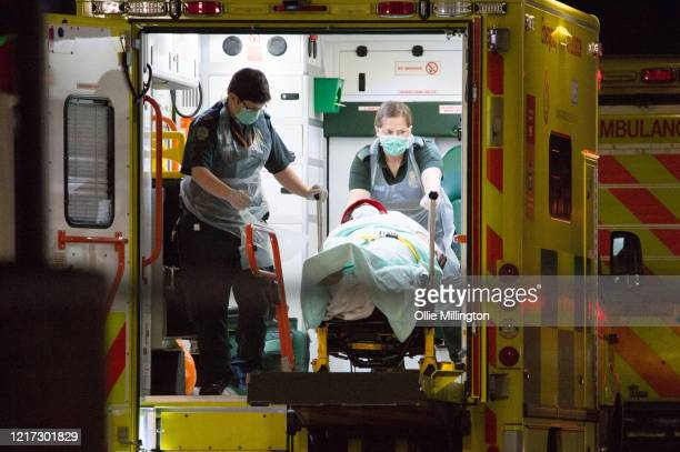 Ambulance workers transport patients outside St Thomas Hospital in Westminster where British Prime Minister Boris Johnson has now been transferred to...