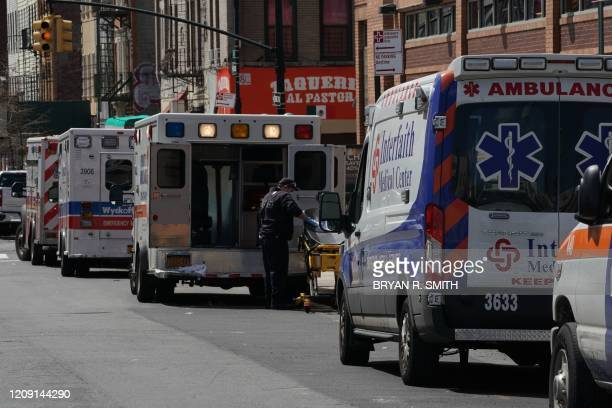 Ambulances are parked outside of Wyckoff Hospital in the Borough of Brooklyn on April 4, 2020 in New York. - New York state's coronavirus toll rose...