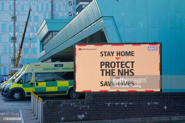 Ambulances line up as a electronic sign funded by the trust gives out coronavirus pandemic information to visitors and staff at the Aintree...
