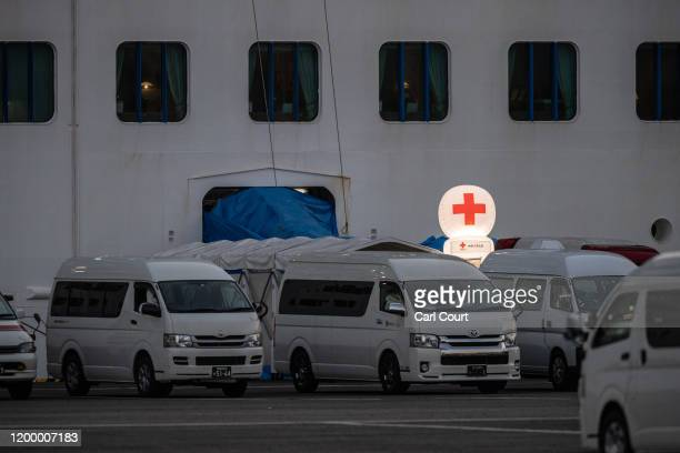 Ambulances wait near a Red Cross balloon hanging next to the Diamond Princess cruise ship as it sits docked at Daikoku Pier where it is being...