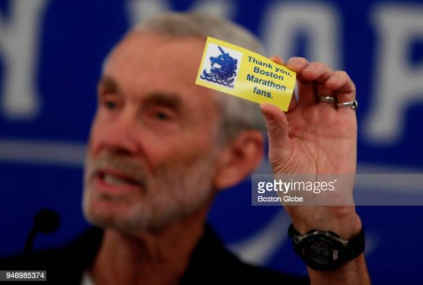 Amby Burfoot holds up a card that he passes out to fans along the route of the Boston Marathon at a press conference in Boston on April 12 2018 Fifty...