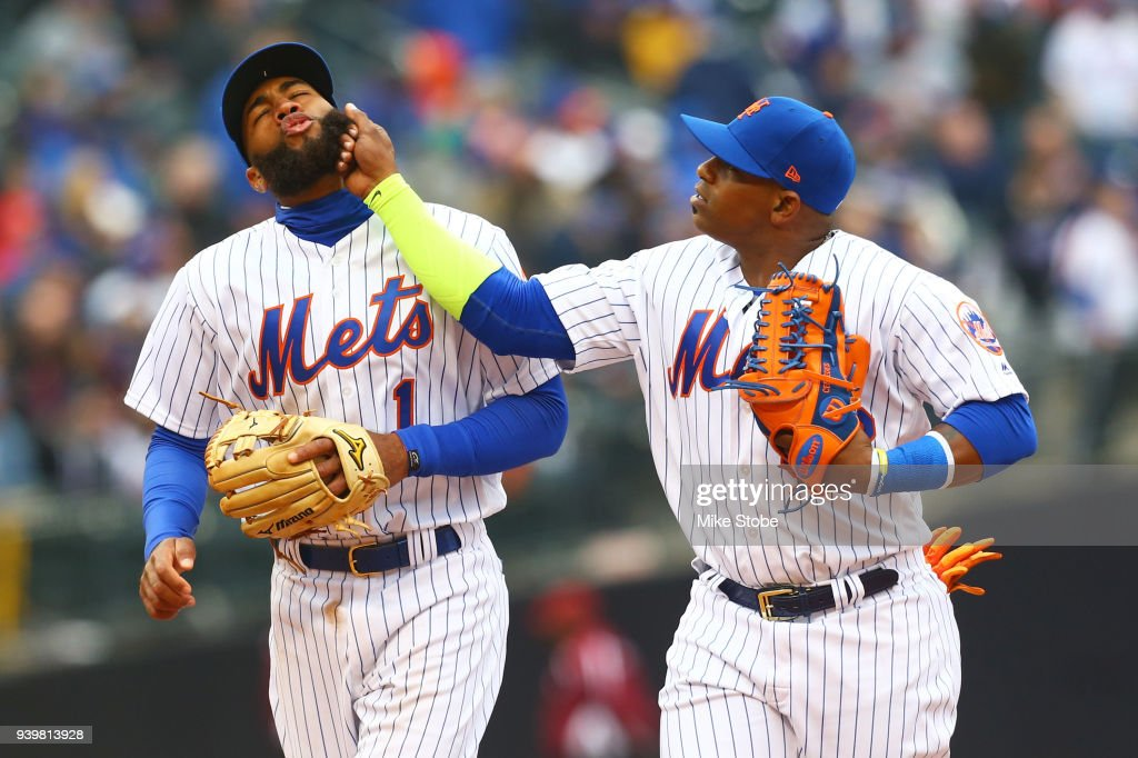 Amed Rosario #1 and Yoenis Cespedes #52 of the New York Mets joke around in eighth inning against the St. Louis Cardinals on Opening Day at Citi Field on March 29, 2018 in the Flushing neighborhood of the Queens borough of New York City.