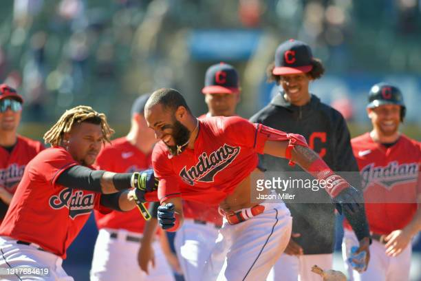 Amed Rosario of the Cleveland Indians celebrates with teammates after hitting a walk-off RBI single in the tenth inning to defeat the Chicago Cubs at...