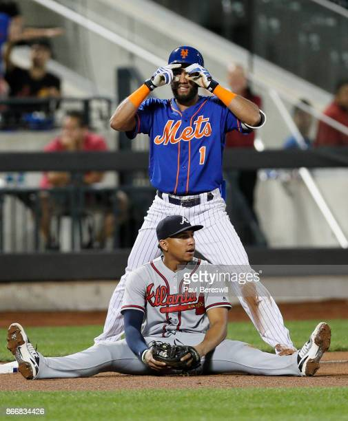 Amed Rosario of the New York Mets celebrates his triple at third base while Johan Camargo of the Atlanta Braves appears frustrated after Rosario beat...