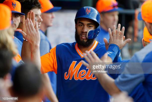 Amed Rosario of the New York Mets celebrates with his teammates in the dugout after scoring a run in the eighth inning against the Washington...