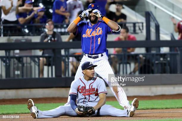 Amed Rosario of the New York Mets reacts after hitting a triple in the seventh inning as Johan Camargo of the Atlanta Braves sits on the field on...