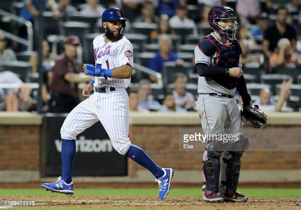 Amed Rosario of the New York Mets scores the tying run in the 10th inning as Roberto Perez of the Cleveland Indians defends at Citi Field on August...