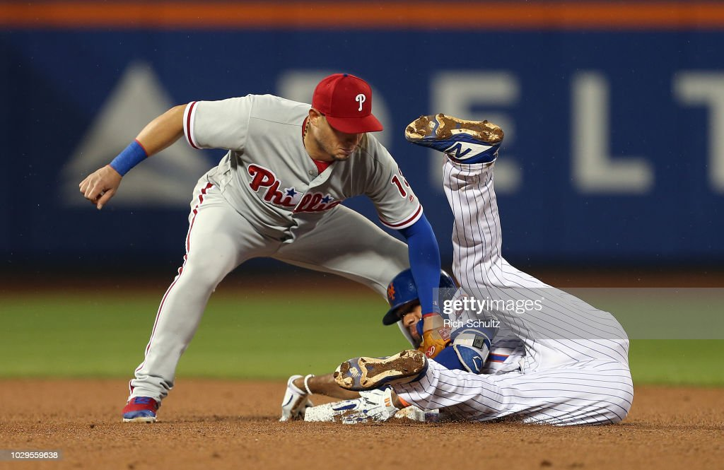 Amed Rosario #1 of the New York Mets slides safely into second base for a double ahead of the tag by shortstop Asdrubal Cabrera #13 of the Philadelphia Phillies during the fourth inning of a game at Citi Field on September 8, 2018 in the Flushing neighborhood of the Queens borough of New York City. The Mets defeated the Phillies 10-5.
