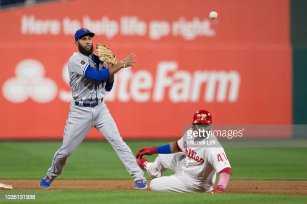 Amed Rosario of the New York Mets turns a double play against Carlos Santana of the Philadelphia Phillies to end the second inning at Citizens Bank...