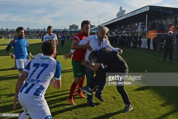 Amedspor's forward Deniz Naki claches with Erzurum's head coach Mustafa Kemal Kilic on May 16 2017 after Amedspor lost the Turkish Super Lig white...