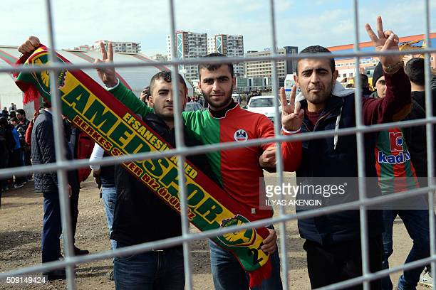 Amedspor's supporters gesture and wave scarves to cheer their team prior to the Turkish Cup football match between Amed Spor and Fenerbahce Zirrat on...