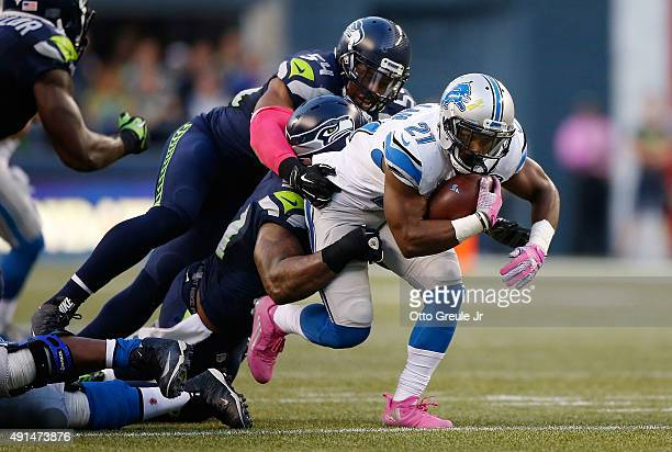 Ameer Abdullah of the Detroit Lions is tackled by Bobby Wagner of the Seattle Seahawks and Bruce Irvin of the Seattle Seahawks as he carries the ball...