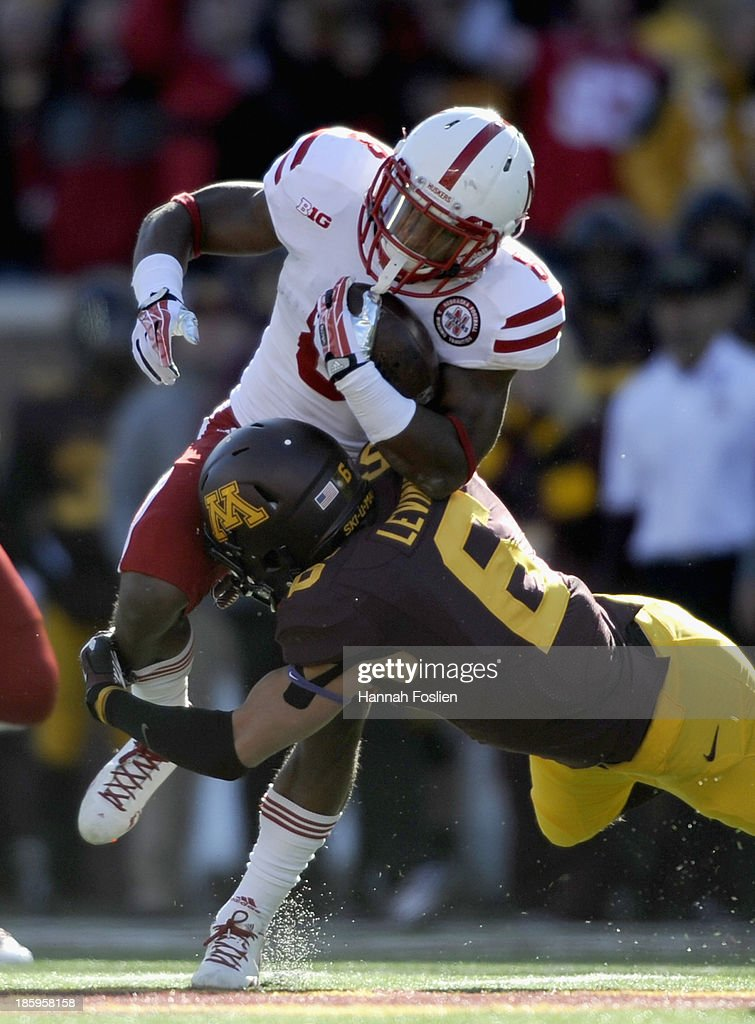 Ameer Abdullah #8 of the Nebraska Cornhuskers avoids a tackle by Grayson Levine #6 of the Minnesota Golden Gophers during the first quarter of the game on October 26, 2013 at TCF Bank Stadium in Minneapolis, Minnesota. The Golden Gophers defeated the Cornhuskers 34-23.