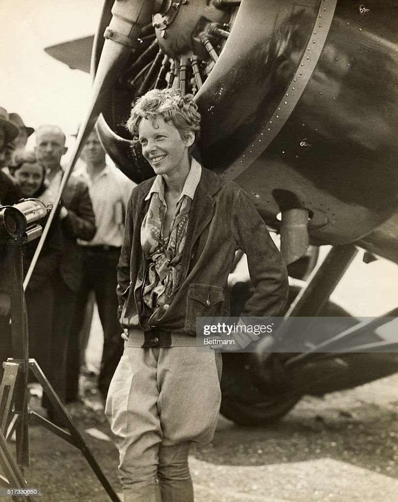 Amelia Earhart (1898-1937), American aviator, smiling as she stands near her plane.