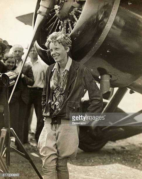 Amelia Earhart American aviator smiling as she stands near her plane