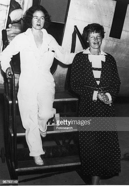 Amelia Earhart and friend descending from an airplane's stairway circa 1935