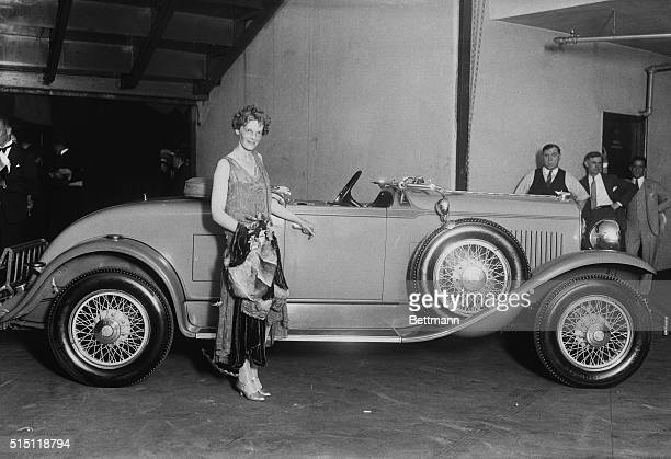 Amelia Earhart famous aviatrix posing at Madison Square Garden with the automobile she received from the Chrysler Co