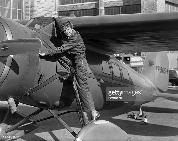 Amelia Earhart first woman to cross the Atlantic Ocean in an airplane She is shown climbing into the cockpit Undated photograph
