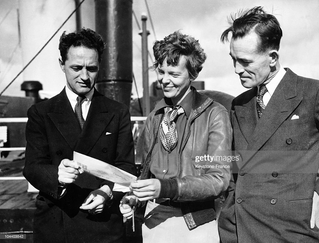 Amelia EARHART is pictured on her arrival in Los Angeles from Honolulu where she crashed on her attempted flight around the world at the equator. With her are two of her aides, Captain Harry MANNING (left) and Fred NOONAN. Miss EARHART will make another attempt to circle the globe when her FLYING LABORATORY has been repaired.