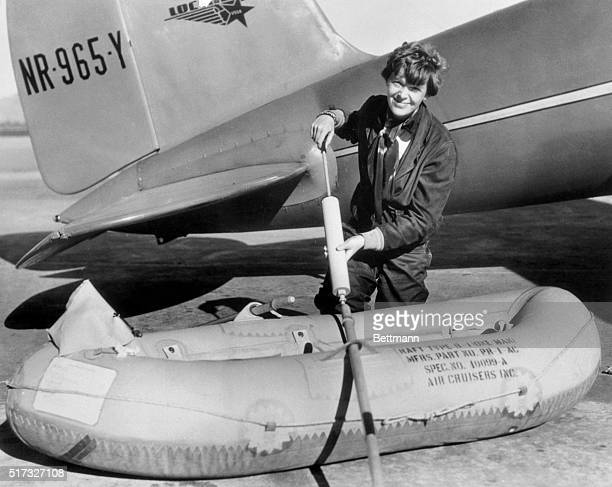 Amelia Earhart is shown here as she inflated the tiny rubber life raft that was part of the equipment of her 'flying laboratory' during preparation...