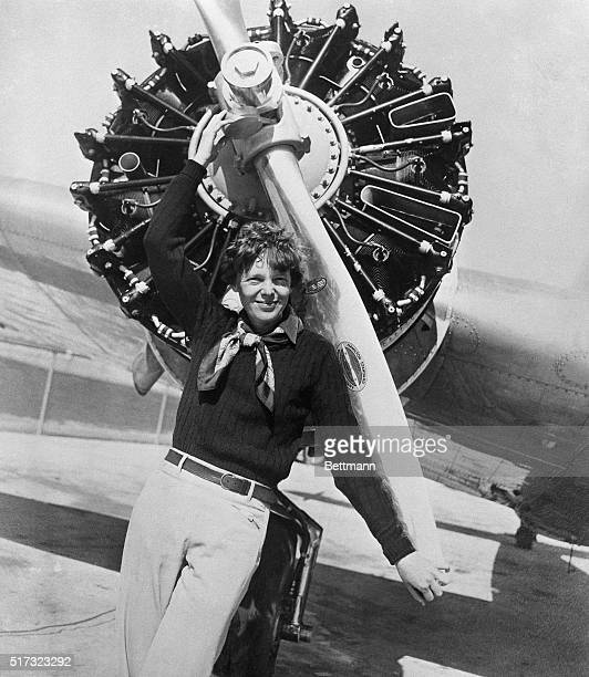 Amelia Earhart leans on the propeller on the right wing engine on her airplane Earhart and her navigator Fred Noonan disappeared on a flight over the...