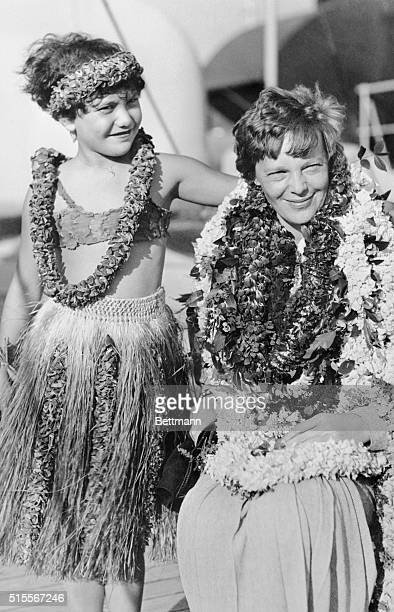 Amelia Earhart Putnam is shown draped with leis as she was greeted to Honolulu upon her arrival in that territory aboard the S S Lurline by little...