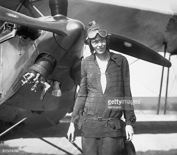 Amelia Earhart stands in front of her airplane