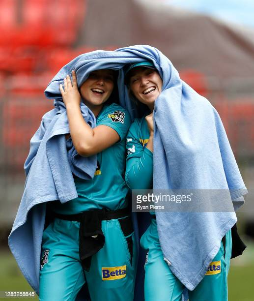 Amelia Kerr and Maddy Green of the Heat keep warm during a rain delay during the Women's Big Bash League WBBL match between the Sydney Thunder and...