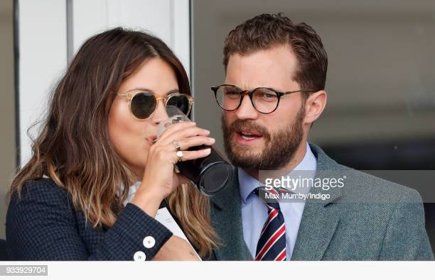 Amelia Warner and Jamie Dornan attend day 4 'Gold Cup Day' of the Cheltenham Festival at Cheltenham Racecourse on March 16 2018 in Cheltenham England...