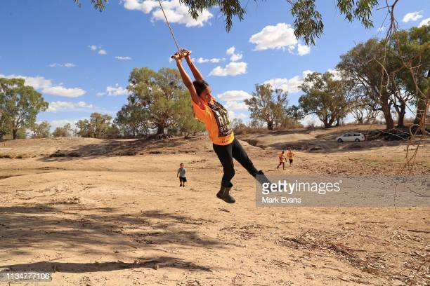 Amelia Whyman swings from a tree onto the dry bed of the Darling -Barka river on March 04, 2019 in Wilcannia, Australia. The Barkandji people -...