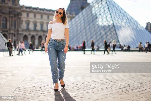 Amelie Lloyd fashion blogger wears a Zar white tshirt sunglasses Zara blue jeans with pearls and Zara black heels at the Louvre on April 2 2017 in...