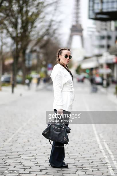 """Amelie Lloyd, fashion blogger, wears Sandro black flared pants, a Jennyfer white pull over with a hood and the printed inscription """"Let's try the..."""