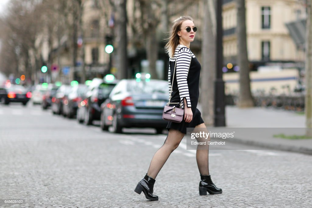 Amelie Lloyd, fashion blogger, wears sunglasses, a Dahlia Girls black dress with a striped collar, fishnet tights, a Valentino rockstud bag, and New Look black shoes, on February 26, 2017 in Paris, France.