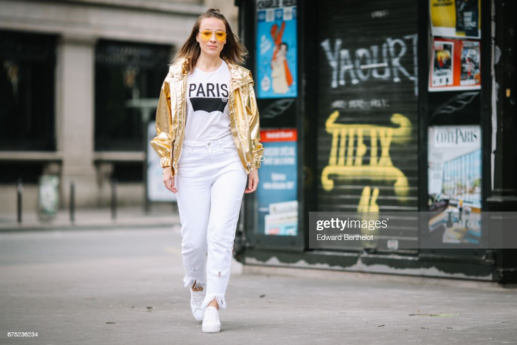 Amelie Lloyd, fashion blogger, wears white sneakers shoes, Zara white denim ripped jeans, a Levis white t-shirt with the print 'Paris', and a Wanda Nylon gold shiny jacket, on April 30, 2017 in Paris, France.