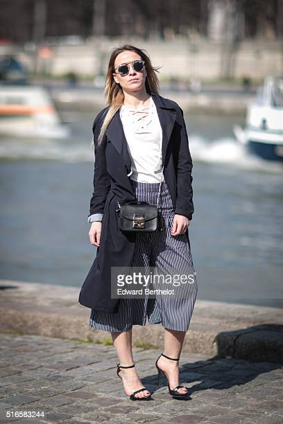Amelie Lloyd is wearing a Jennyfer top Jennyfer pants Dior sunglasses a Zara trench coat Zara heels and a Furla bag during a streetstyle session on...