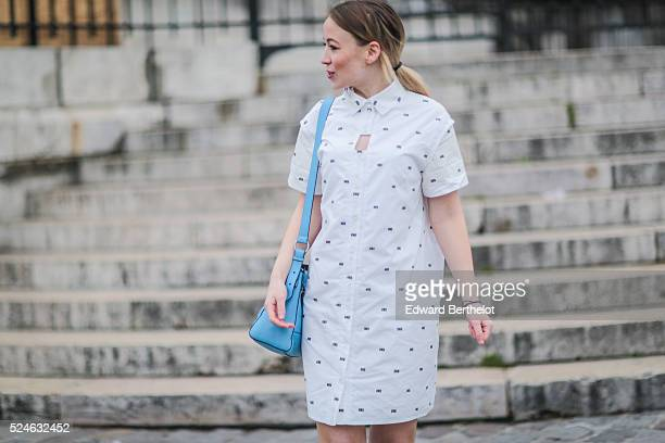 Amelie Lloyd is wearing a Kenzo blue bag a Kenzo white dress and HM white shoes during a street style session on April 26 2016 in Paris France